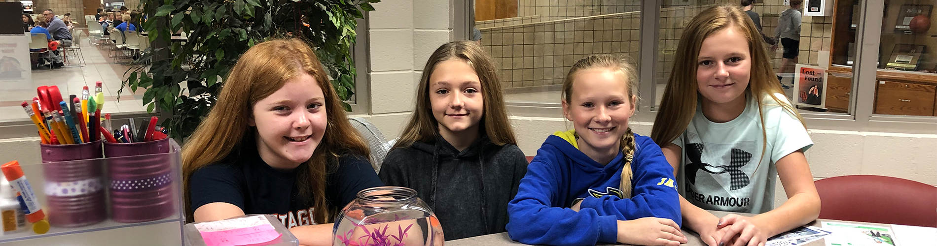 Middle school students pose with the fishbowl in the office.