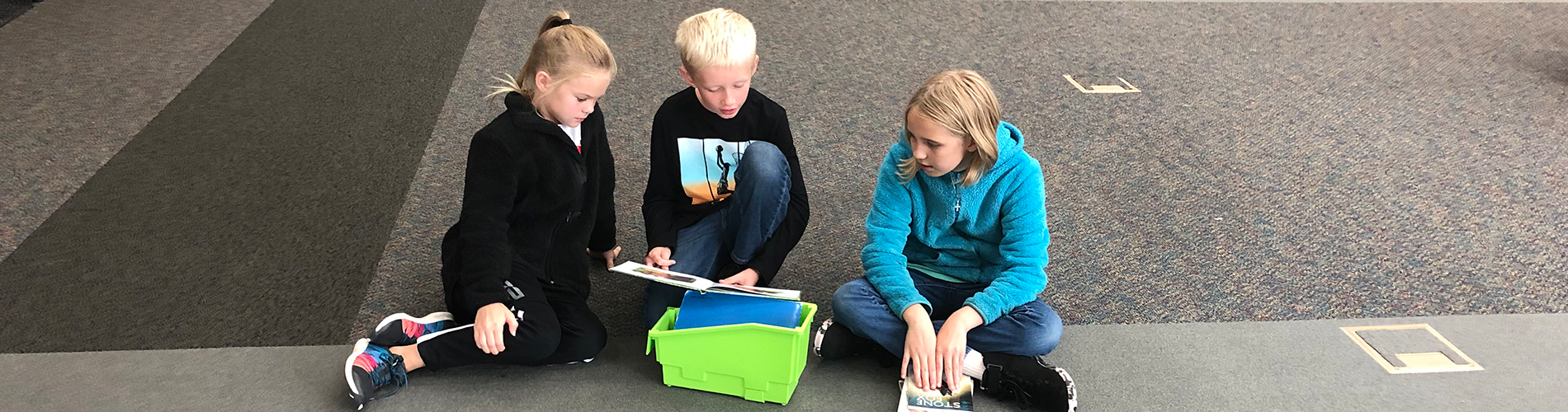 Elementary students read books to other students.