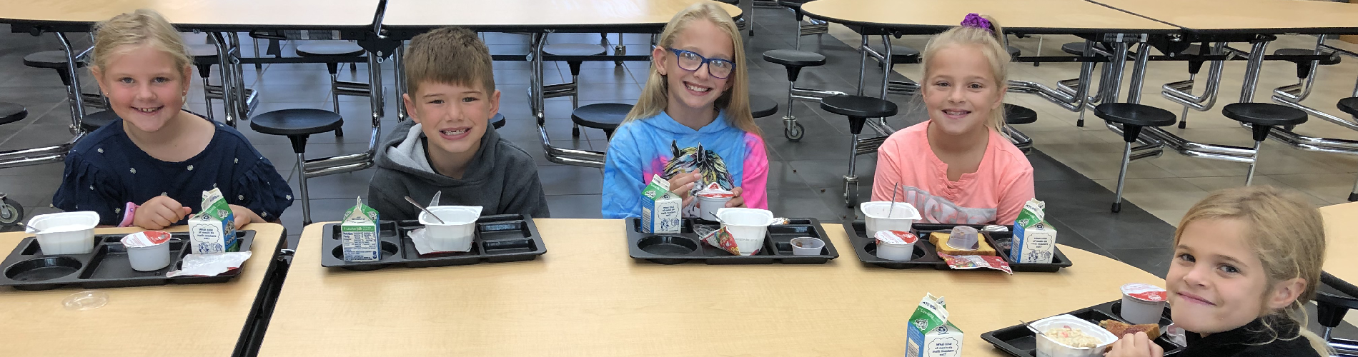 Elementary students smile for the camera while eating breakfast.