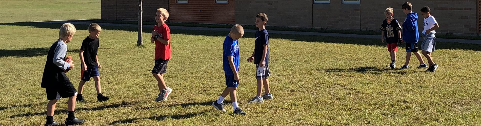 Elementary students play football at recess.