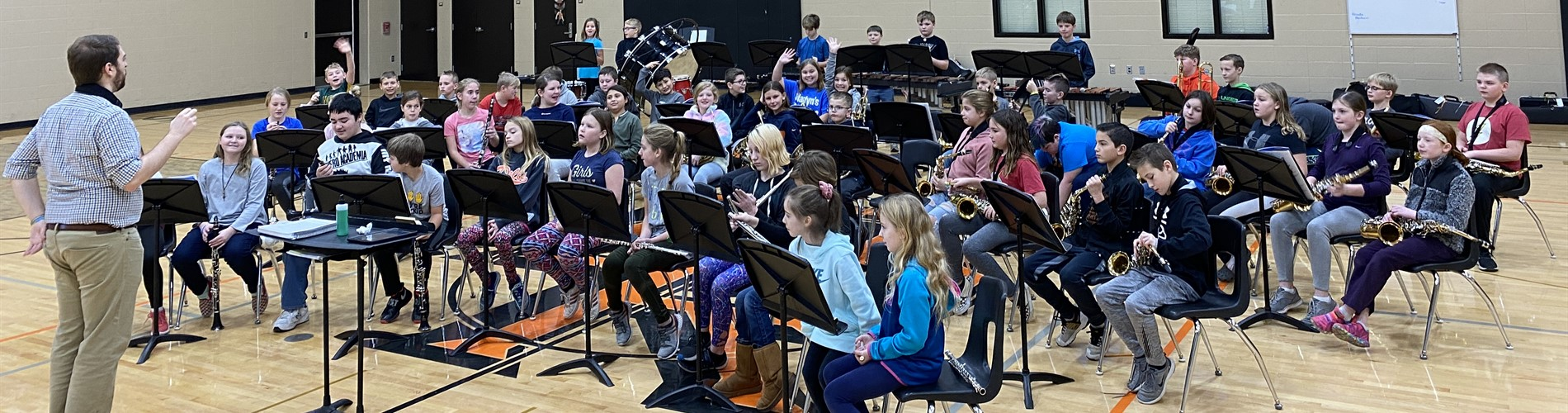 5th-grade students practice for their band concert in the middle school gym.