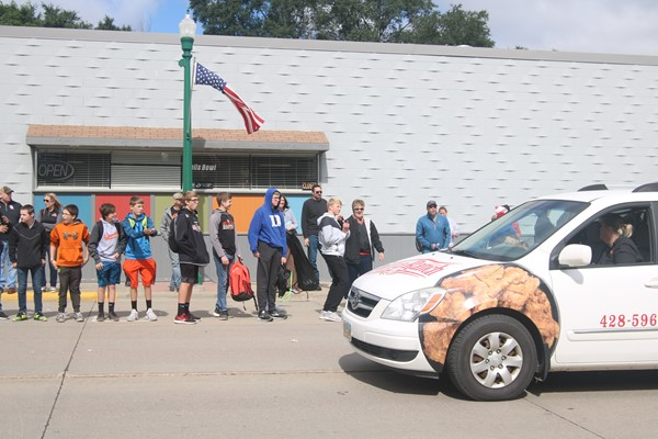 Students watch the Pizza Ranch van drive through the parade.